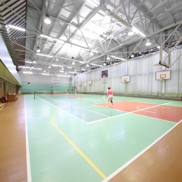 Two women playing tennis in the indoor tennis court